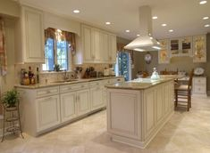 Lighting plays a big role in any design. At the far end is a wall unit with glass doors, the use of lighted cabinets draws the eye through this design, creating a spacious kitchen, and a clean and luxurious look.