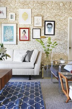 Gold wallpaper is the perfect foil for this cream mid-century modern sofa & wood coffee table