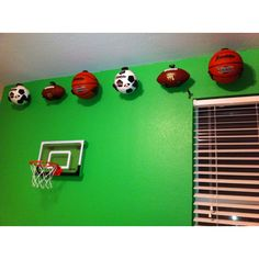 We wanted the decorations in Zeke's sport's themed room to be 3D so we made a border out of real sports balls purchased from Wal-Mart and hung them with ball claws purchased online at theshelvingstore.com.