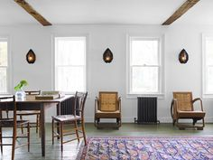 White Room Decorating Ideas - Vintage Style Decor - Country LivingThe living-dining area is furnished with a far-flung mix: Indonesian rush-back loungers, tin sconces from Mexico, and a Persian kilim rug. The farm table and its attendant cane-seat chairs, however, are locally sourced antiques.