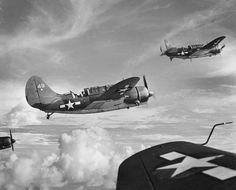 August 24, 1944: Curtiss Helldivers from the Fast Carrier Task Force 58 are seen midair on a mission over Saipan, in the Mariana Islands. The Helldiver was a robust aircraft with a reputation of absorbing punches and coming back for more. She continued in service past 1945, mainly with air forces of allied countries.