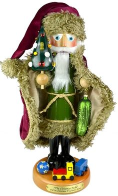 Steinbach Christmas Pickle Nutcracker - Second in the Christmas Traditions Series, The Christmas Pickle nutcracker is a limited edition nutcracker of 5,000 pieces. This richly decorated Santa holds a small decorated tree in his right hand, which naturally has a pickle ornament hidden in it's branches. Online only. $267.00