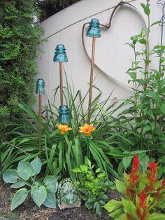 Old electric glass insulators on copper pipes =  unique garden art