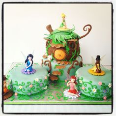 Pixie Hollow cake. House is vanilla with vanilla buttercream, and side cakes is chocolate cake with vanilla buttercream, all cakes covered in fondant and fondant details. Fairy toppers were toys.