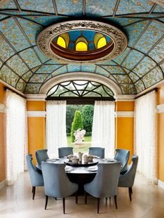 This airy breakfast room is grounded by a custom walnut breakfast table and chairs clad in blue grey chenille. The ceiling is a beautiful mosaic tile scene banded in solid brass.