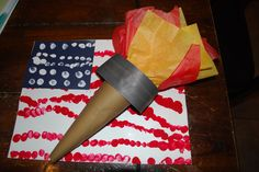 Olympics craft Fingerprint flag made as backdrop. Torch created with rolled paper and stuffed with tissue paper.