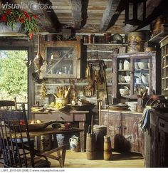 Interior shot of Primitive rustic kitchen, with old corner cupboard with old pottery and cooking utensils etc, log and chink walls, distressed cabinets, spongeware, wooden bowls and utensils, butter churns, old tins