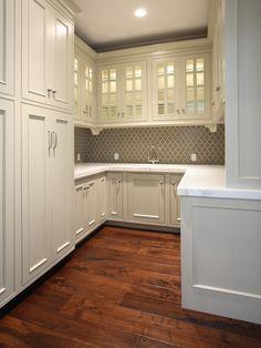 grey backsplash, marble counters, glass cabinets.