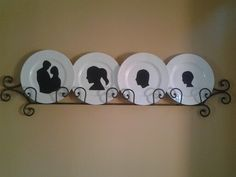 Four Goodwill white plates=$4. The yard sale plate rack was free with my purchase of plates which I resold (btw.)  One bottle Modge Podge.  Leftover black scrapbook paper. Cut silohuettes of my family from my favorite photos. And voila! A custom art piece.