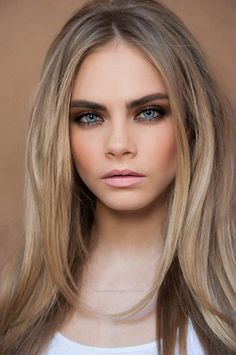 Light hair - parted down the middle , defined eyebrows with smokey eyes and nude lip.