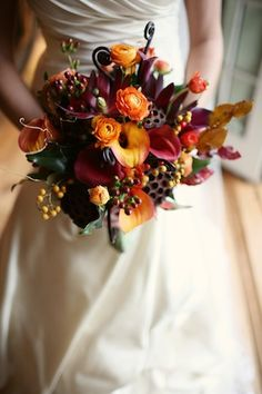 orange ranunculus, flame and purple calla lilies, fiddlehead ferns, and an assortment of Fall foliage.