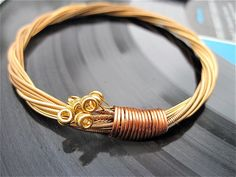 """Recycled Acoustic Guitar String Bracelet"" I could do this...if I had some guitar strings...and I was good at making stuff."