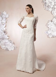 Sweetheart style 5989 A Queen Anne neckline with fitted three-quarter sleeves in tulle and  lace on this slim A-line gown. The back features a keyhole, buttons  covering the back zipper, and a chapel length train.