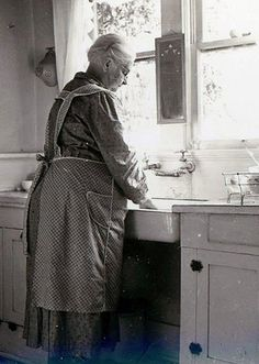 Wearing an apron to protect your dress  ....my grandma always wore an apron like this. She also wore her pearls everyday....great memories...