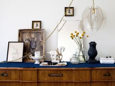 Eclectic design encompasses a variety of periods and styles. Stick to a few neutrals, like the black, white and navy palette of this dresser vignette, to pull an eclectic look together. Another key component to this style is to mix in different finishes and textures. Design by Emily Henderson.
