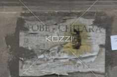 peeled poster on wall. - Detailed shot of scratched poster on concrete wall.