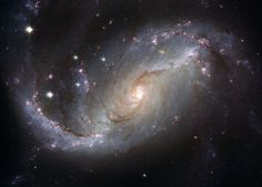 Many spiral galaxies have bars across their centers. Even our own Milky Way Galaxy is thought to have a modest central bar. Prominently barred spiral galaxy NGC 1672, pictured above, was captured in spectacular detail in image taken by the orbiting Hubble Space Telescope. Visible are dark filamentary dust lanes, young clusters of bright blue stars, red emission nebulas of glowing hydrogen gas, a long bright bar of stars across the center, and a bright active nucleus that likely houses a supermas
