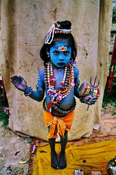A child in the disguise of Lord Krishna , at a colorful rally of the Hindu devotees which passed through different areas of Dhaka city , to mark the birthday of Lord Krishna . According to Hindu belief on this promising day Lord Krishna descended into this world some 5 , 500 years ago to establish love , truth and justice .