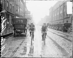 Two boys ride bikes along a street in the rain during a street car strike in Chicago, c. June 1915. Photograph from the Chicago Daily News. DN-0064589  #chicago #history #biking #bikeweek