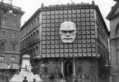 The headquarters of Benito Mussolini and the Italian Fascist party in Italy.    The imposing face on the front entrance is that of Benito Mussolini himself.    1934.