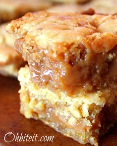 CARAMELLO BLONDIES 1 Box of Yellow Cake Mix (18 oz) 60 individually wrapped KRAFT Caramels..a full bag plus 10, 1 cup finely chopped Pecans 1/2 cup white Chocolate Chips 1/2 cup melted butter 1/3 cup Evaporated Milk 1/2 cup Evaporated Milk (additional) 1/4 cup Powdered Sugar..for dusting Caramello Candy Bars for garnish..optional A square 9×9 baking pan.