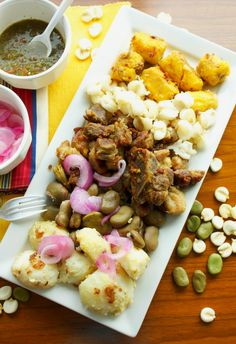 Fritada - Ecuadorian pork fry with hominy, lima beans, sweet plantains, potatoes, aji sauce and pickled onions.  Delicious!