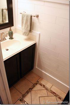Half bath with DIY plank walls, wrapped in molding, DIY inlaid tile rug, black vanity and pocket door