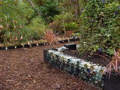 a raised garden made from wine bottles