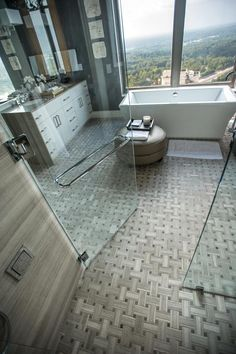 A basket weave floor design connects the spacious bathroom to the enclosed walk-in shower. #HGTVUrbanOasis