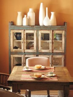 kitchen space with orange wall and rustic pottery