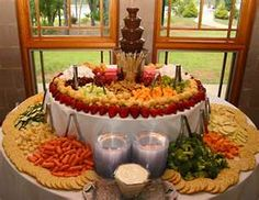 Cute fruit and veggie appetizer table set up. The chocolate fountain's a nice touch.