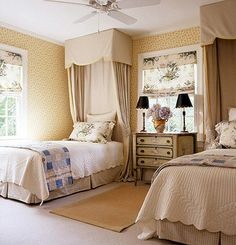 I love this romantic space! Delicate wallpaper, draping fabrics, pale creams and symmetry make for a stunning guest room.