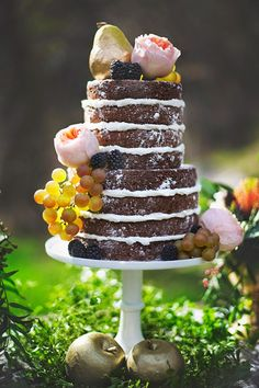 Chocolate naked wedding cake accented with florals and fruits.