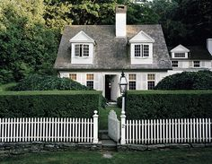 Adorable Cape Cod cottage with gray shingles, white shutters, white picket fence, and black lanterns...