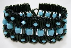 Turquoise & Black Beadwoven Cuff Bracelet.  This cuff bracelet is beadwoven with seed beads in the color of black, bugle beads in the color of black, and Swarovski crystal beads in the color of turquoise.  Wrist size is 7¼ inches when clasped. Width is 1¼ inches.  Clasp is a beaded bead and loop.  #thecraftstar #beunique #Noveenna