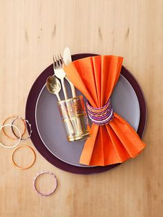 Spice up your holiday buffet with these globally inspired ideas. Tuck flatware sets into embellished water glasses — mix and match from your stash or, if you can afford a splurge, buy Moroccan tea glasses. Then, for Bollywood flair, slip child-size Indian bangles around pleated persimmon-hued paper napkins.