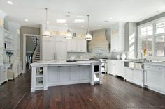 A luxurious kitchen with white marble countertops, hand-scraped wood flooring, and an elegant stone hood in the corner.