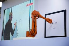 """Austrian artist Alex Kiessling is shown working on a drawing live from Vienna on a big screen in Trafalgar Square, London, as robot arms in London, right, and Berlin replicate his work, Thursday, September 26, 2013.  The project has been given the title """"Long Distance Art"""" and utilizes the IRB 4600 robotic arms, produced by the company ABB for industrial manufacturing in areas such as automotive, plastics, metal fabrication and electronics. (Photo by Matt Dunham/AP Photo)"""