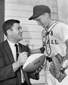 Omahan Pat Fischer, a defensive back for the NFL's St. Louis Cardinals, autographs a football for Bob Stolp in May 1967. The 11-year-old was a third baseman and pitcher for Jim's Rexalls in the Suburban Baseball Association. He was hesitant to sign up for Little League in 1967 after he lost his hand in an accident the previous summer. THE WORLD-HERALD