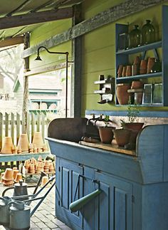 blue dry sink with stacks of clay pots