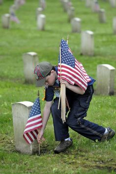 A young boy places American flags on the graves of U.S. soldiers...