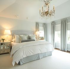 Ashley Goforth Designs!  ivory & blue bedroom design with light blue gray headboard, Oly Studio Elisabeth ivory mirrored cabinets nightstands, glass column lamps, crystal chandelier, ivory wool rug, blue walls paint color, silk blue damask pillows, velvet gray bolster pillow and blue drapes.