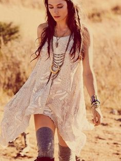 Asymmetric flowy white knit dress, long and large necklaces, knee high socks and boots