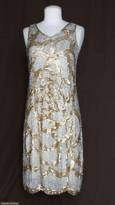 SILVER BEAD & GOLD SEQUIN EVENING DRESS, c. 1925  Completely covered in vermicelli patterned silver bugle beads w/ crimped gold sequins forming center floral & arched bands, shallow scalloped hem  augusta-auction.com