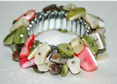 Vintage Beaded Stretch Accordion Silver Tone Metal Bracelet. The bracelet is festooned with Polished Shell Nugget beads. Most of which are natural and a few are dyed pink or green.  It is a fun...