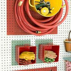 Martha Stewart - garages - utility, wall, peg boards, yellow, bucket, red, garden, hose, red, small, cubbies, garden gloves, hooks, garden tools, peg board, garage peg board, well organized garage, organized garage,