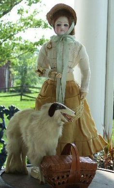 19th century fashion doll with dog and picnic basket.