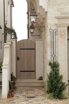 Door leading to the back yard, Mediterranean style, wooden outdoor door, rough luxe design