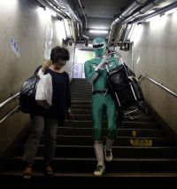 Masked hero helps carry bags, babies up and down Tokyo subway stairs