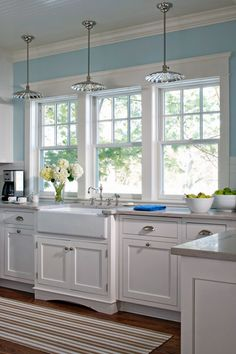 Lovely farmhouse sink with a view, white cabinets, pale blue walls